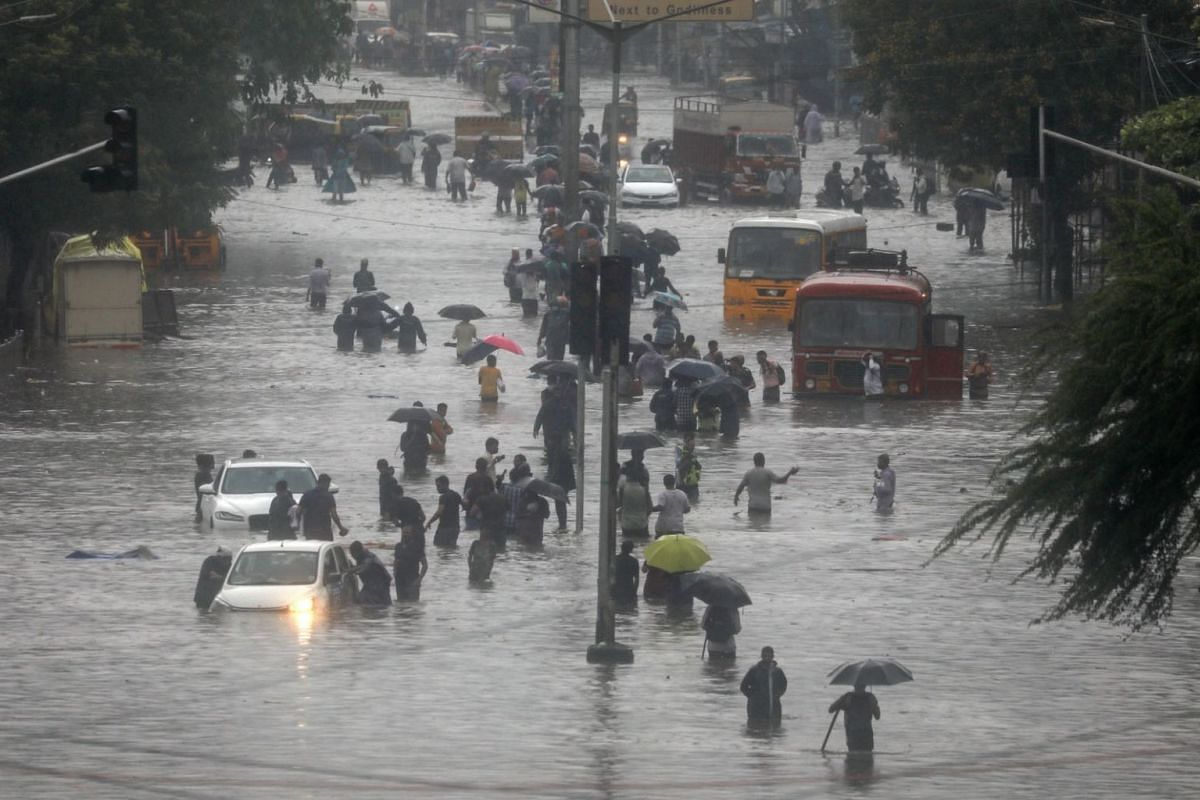 Indian people wade through a flooded street during heavy rain in Mumbai, India, on June 9, 2021.