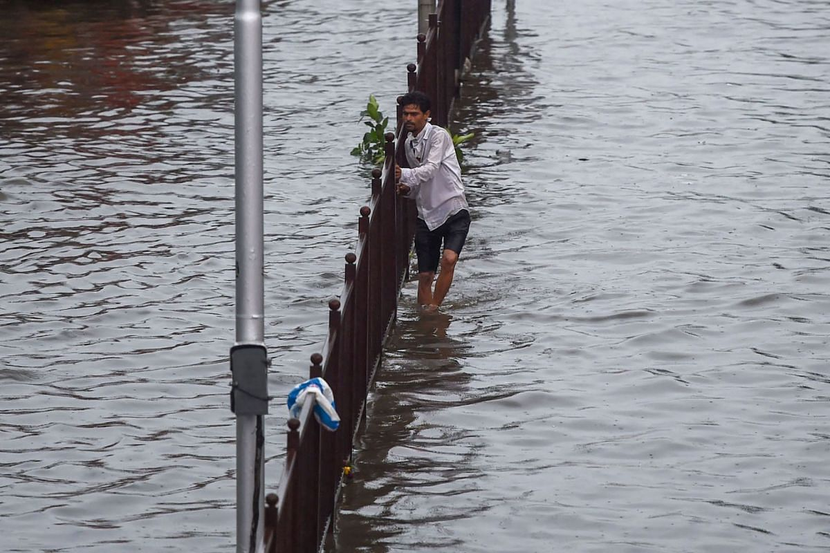 A man holds on to a barrier as he navigates a flooded road following heavy monsoon rains in Mumbai on June 9, 2021.
