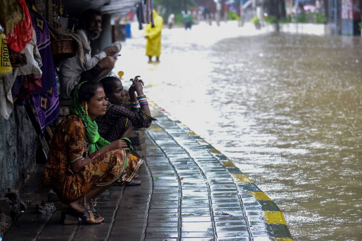 Homeless people shelter unnder a flyover during a heavy monsoon rainfall in Mumbai on June 9, 2021.