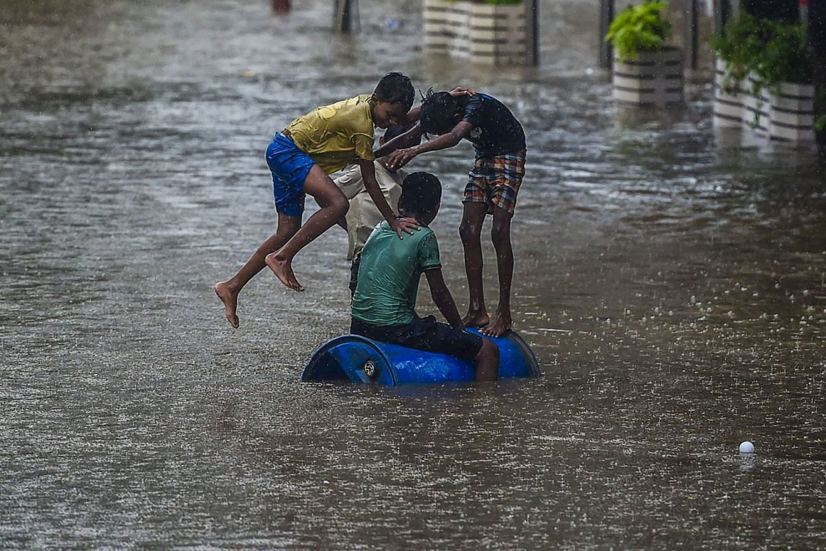 Children play on a flooded street during heavy monsoon rains in Mumbai on June 9, 2021.