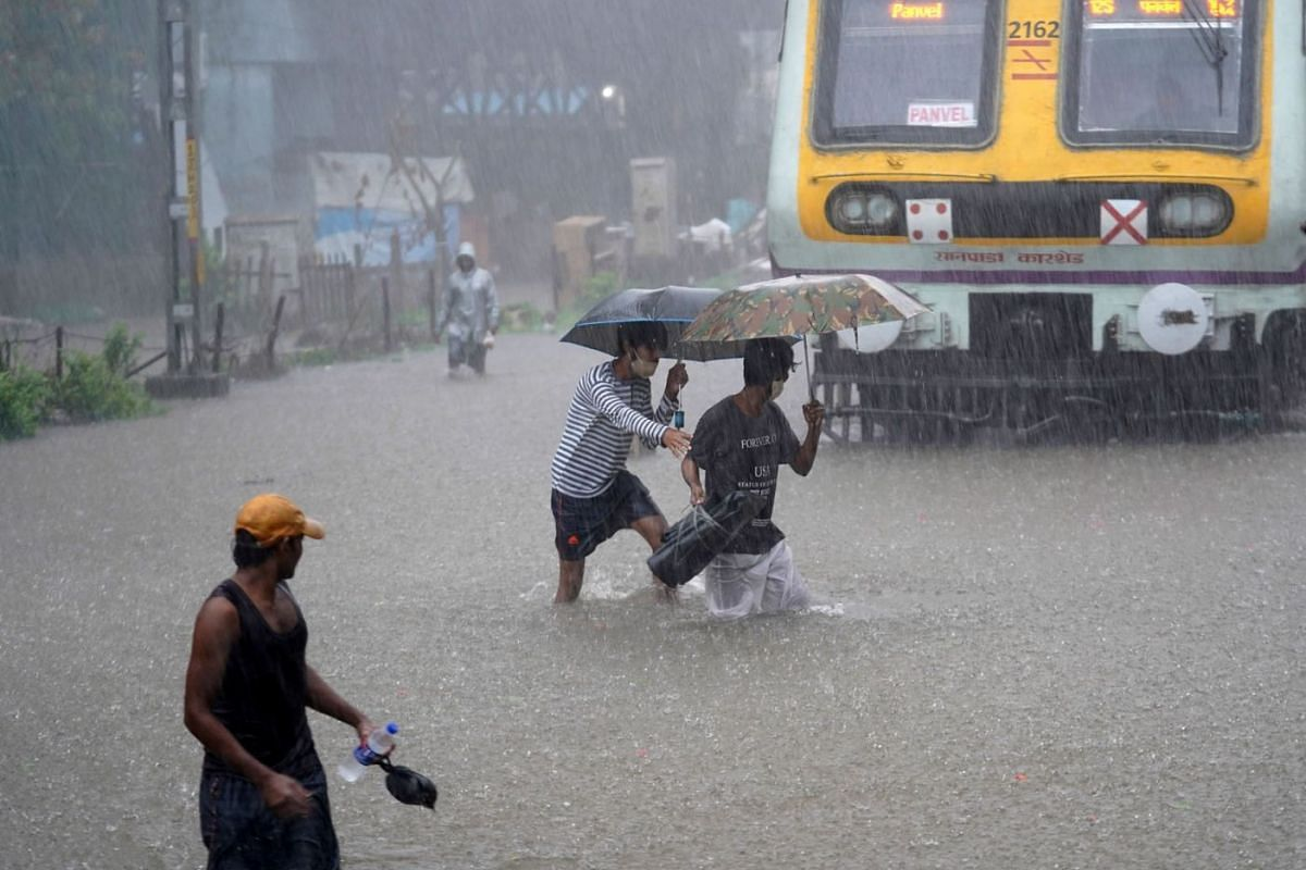 People cross waterlogged railway tracks next to a parked passenger train during heavy rains in Mumbai, India, on June 9, 2021.