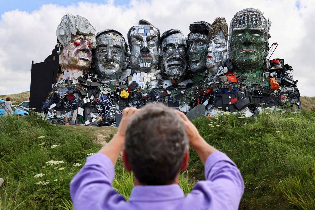 """A man photographs """"Mount Recyclemore"""", an artwork depicting the G7 leaders looking towards Carbis Bay, made from electronic waste by Joe Rush and Alex Wreckage, ahead of the G7 summit, at Hayle Towans in Cornwall, Britain, June 8, 2021."""