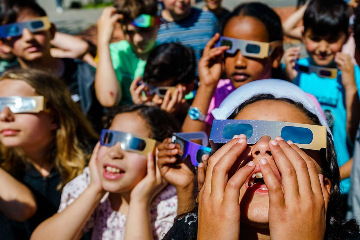 Pupils of primary school IBS Ababil, look at the solar eclipse with special glasses, in Schiedam, The Netherlands, on June 10, 2021. For the first time since 2015, a partial solar eclipse can be seen again, with the sun partly obscured by the moon.
