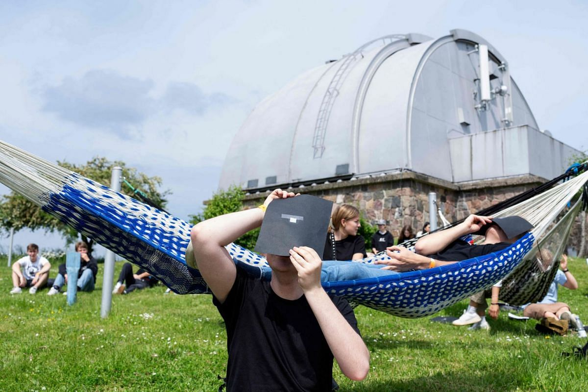 A child look through a filter as people sit waiting to see the partial solar eclipse at the Brorfelde Observatory in Tollose, Denmark, on June 10, 2021.