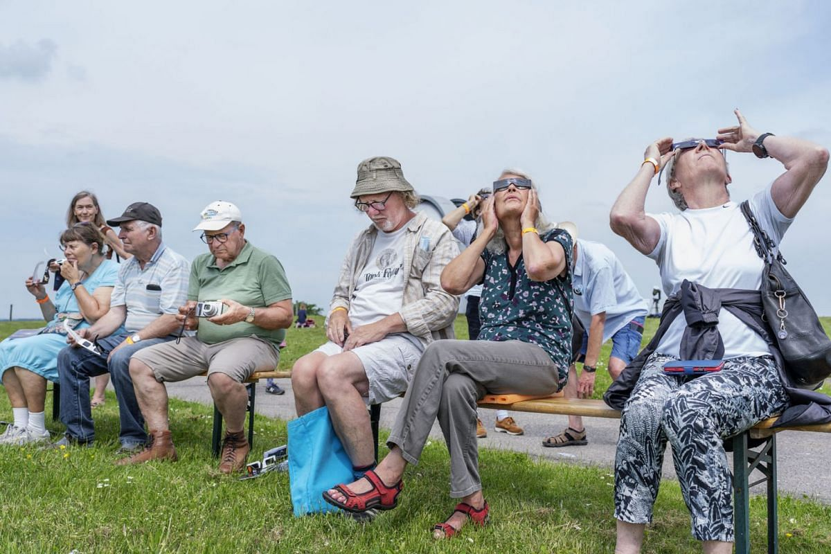 People watch the partial solar eclipse from Brorfelde Observatory at Toelloese in Denmark, on June 10, 2021.