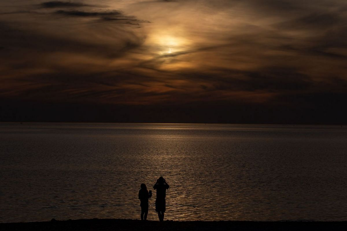 People watch the partial solar eclipse through the clouds at sunrise from the shoreline in, Winthrop, Massachusetts, USA, on June 10, 2021.