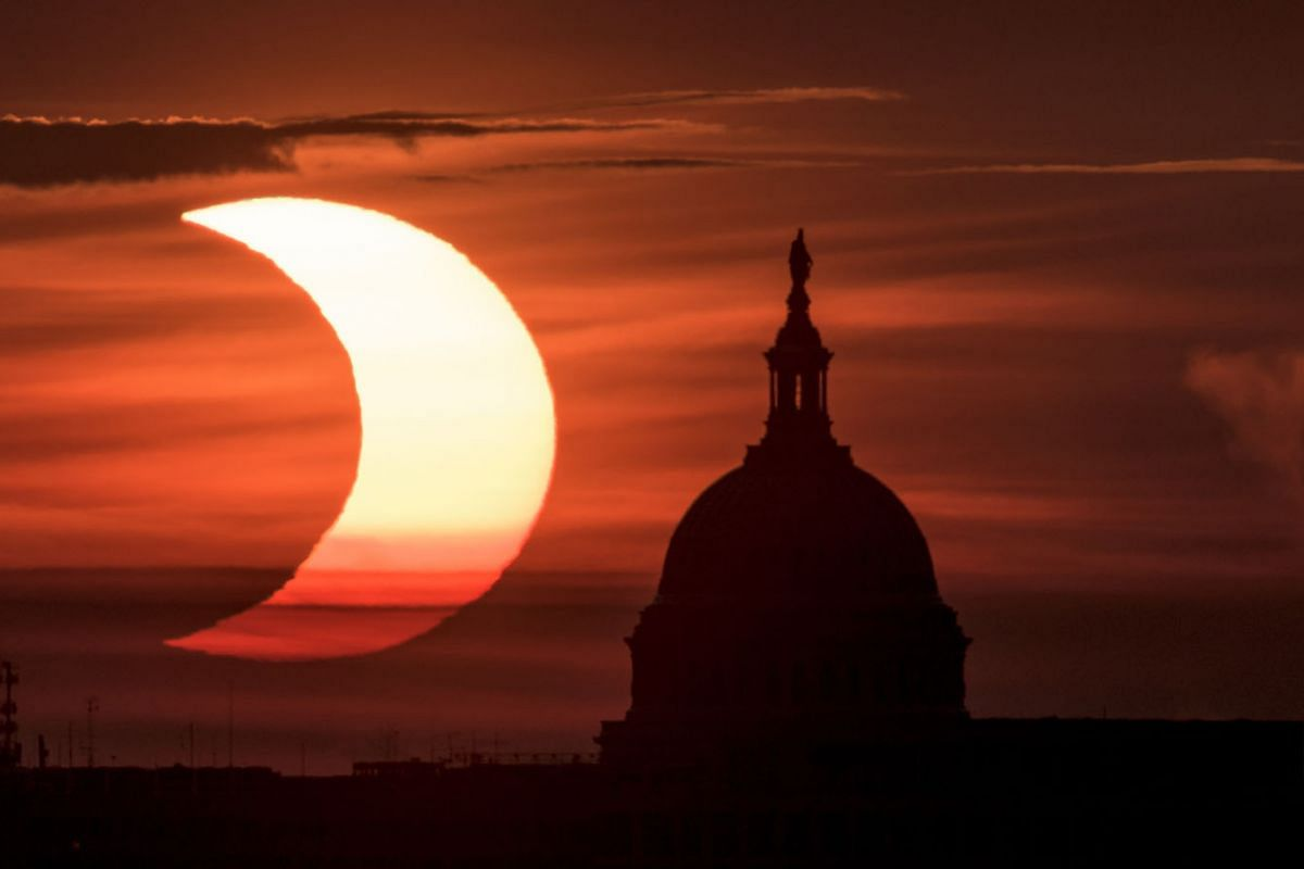 A handout picture made available by the National Aeronautics and Space Administration (NASA) shows a partial solar eclipse as the sun rises to the left of the United States Capitol Building, June 10, 2021, as seen from Arlington, Virginia.