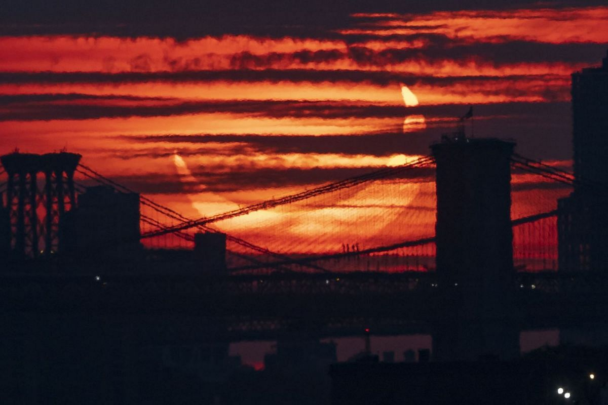 A partial solar eclipse rises over bridges crossing the East River in New York, New York, USA, June 10, 2021. A partial solar eclipse occurs when a portion of the Earth is engulfed by the shadow (penumbera) cast by the Moon as it passes between our p