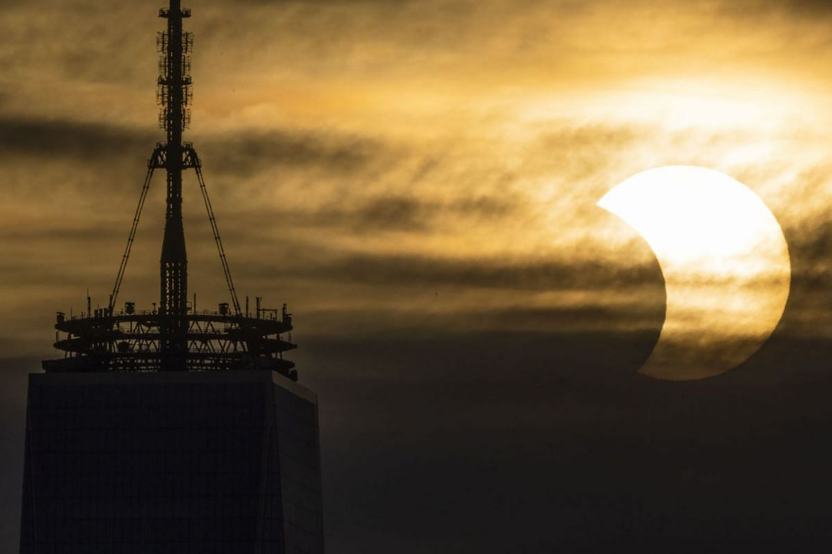 A partial solar eclipse rises over One World Trade Center in New York, New York, USA, June 10, 2021.