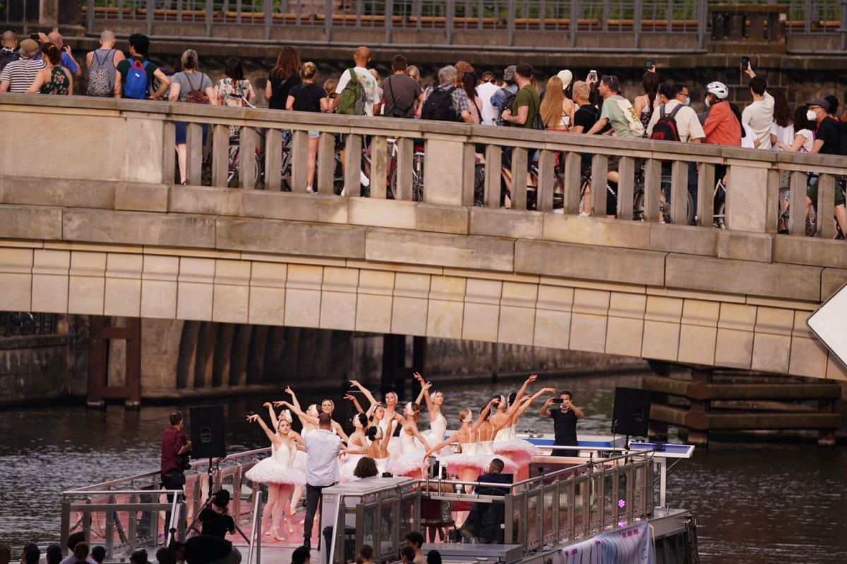 Dancers of the Staatsballett Berlin ballet company perform on an excursion boat on the river Spree as they pass under a bridge full of spectators in Berlin, Germany, on June 10, 2021.