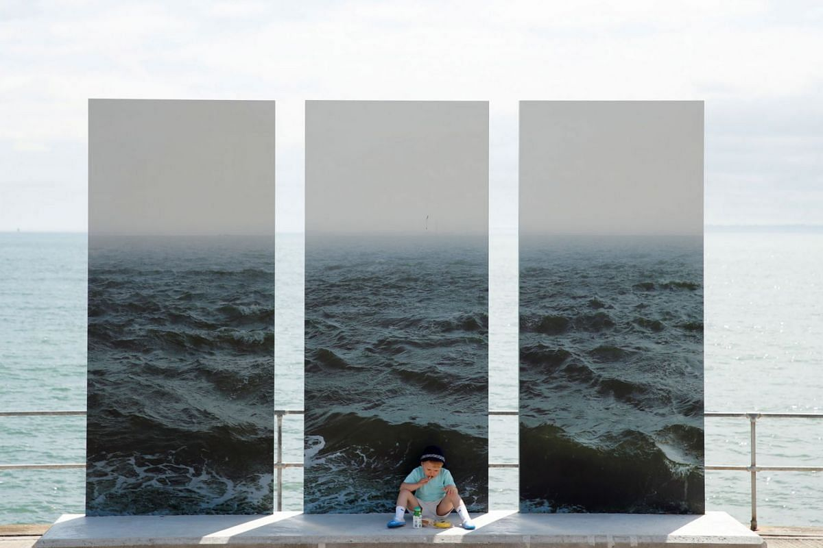 Marshall sits and eats his lunch in front of a piece of artwork entitled In The End Is The Beginning by Nadav Kander during the Estuary 2021 Festival in Shoeburyness, Britain, on June 10, 2021.