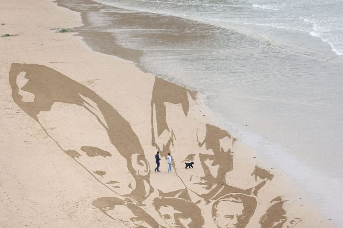 An incoming tide washes away a part of a giant beach sand artwork depicting the faces of the G7 leaders, created by campaign group Avaaz, at Watergate Bay Beach, Newquay, Britain, on June 10, 2021.