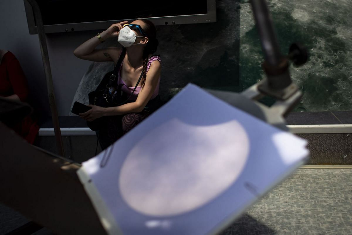 A woman observes the partial solar eclipse with special glasses behind a projection of the eclipse from a telescope at an observatory in Prague, Czech Republic, on June 10, 2021.