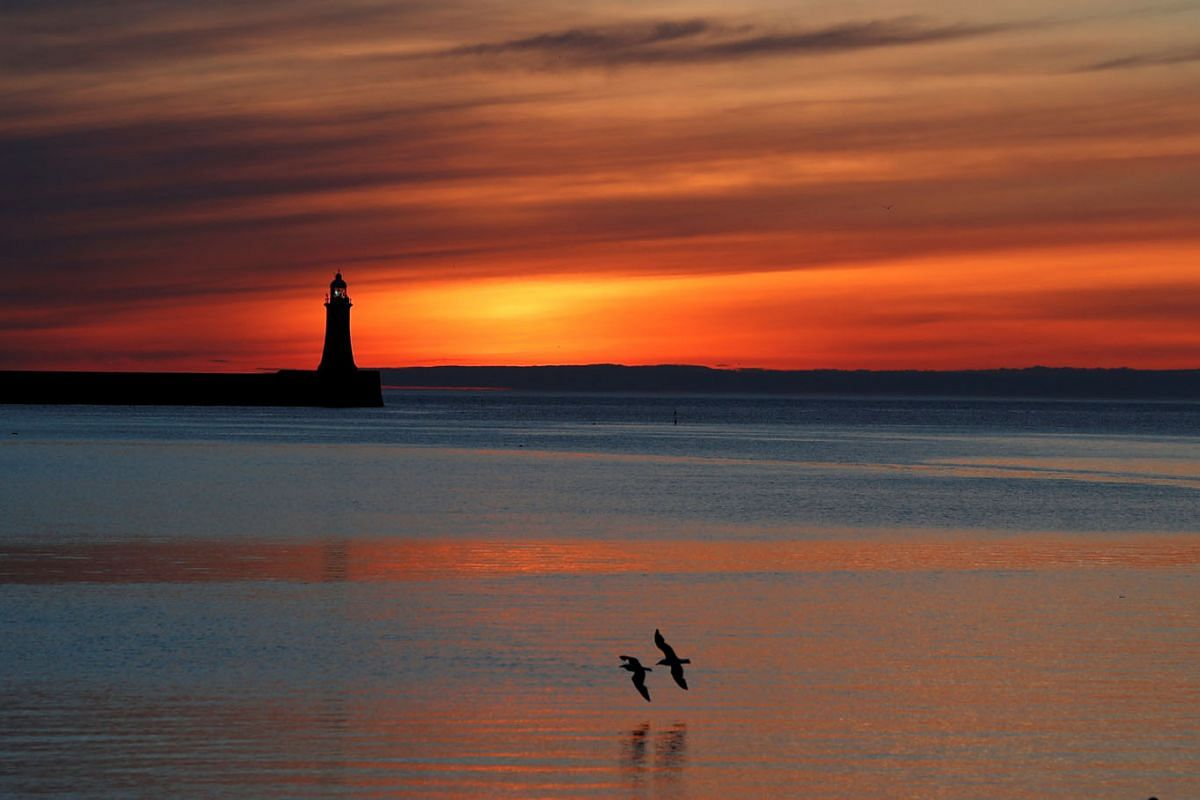 Sunrise over South Shields Lighthouse in Sunderland, Britain, on June 10, 2021.