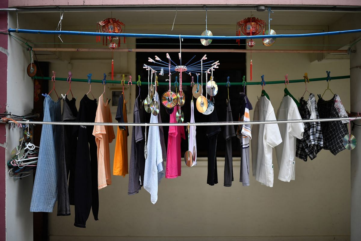 Compact discs hanging among clothes left outside a flat at Block 44 Tanglin Halt Road to dry, possibly to prevent the birds from dirtying the newly washed clothes.