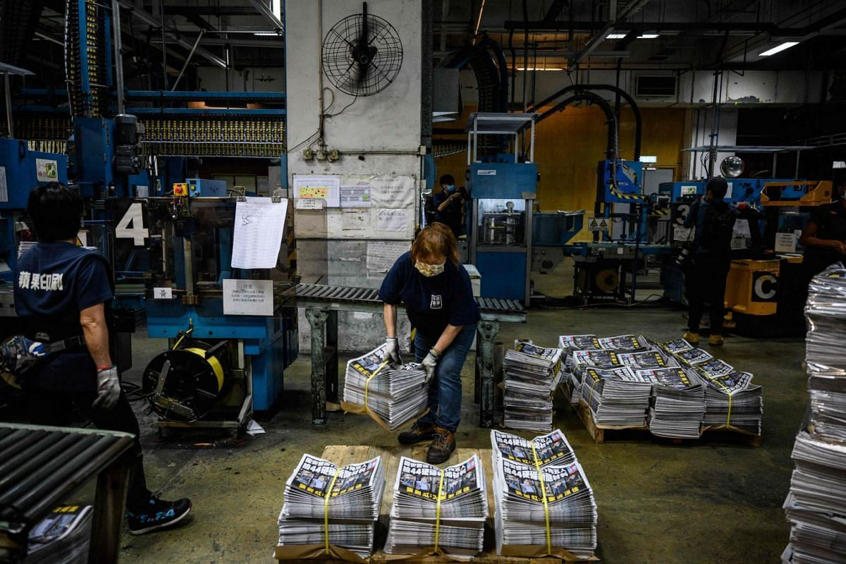 An employee arranges bundles of the Apple Daily newspaper at a news stand in Hong Kong, China, on June 18, 2021. The popular 26-year-old paper increased its Friday press run to 500,000 copies, up from 80,000 the previous day. China took another step
