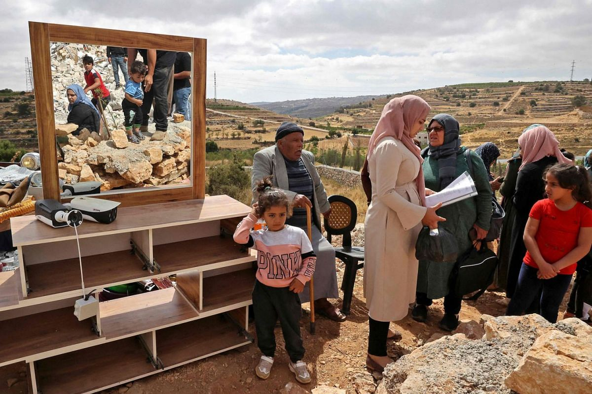 """Members of a Palestinian family check their belongings after Israeli machinery demolished their house located within the """"Area C"""" of the occupied West Bank, where Israel retains full control over planning and construction, near the village of Halhoul"""