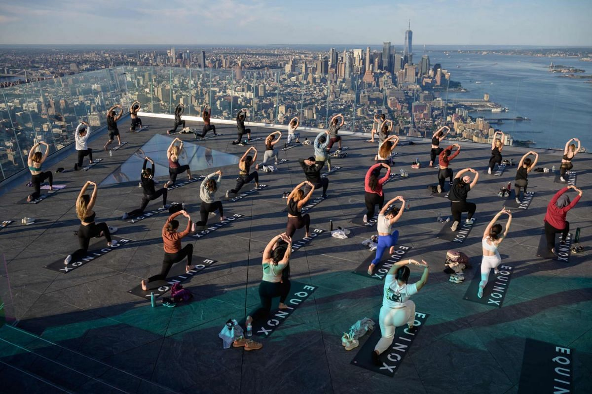 Yoga practitioners attend a class on the Edge Observation Deck, billed as the 'highest outdoor sky deck in the Western Hemisphere' at 1,131 feet (345 meters), and overlooking the Manhattan skyline, in New York, on June 17, 2021.