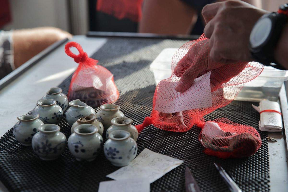 A label, containing information on when and where artefacts were recovered, is placed into a mesh bag with the artefacts. Important pieces are bubble-wrapped, while the red mesh bags are placed in crates to be transported back to the mainland.