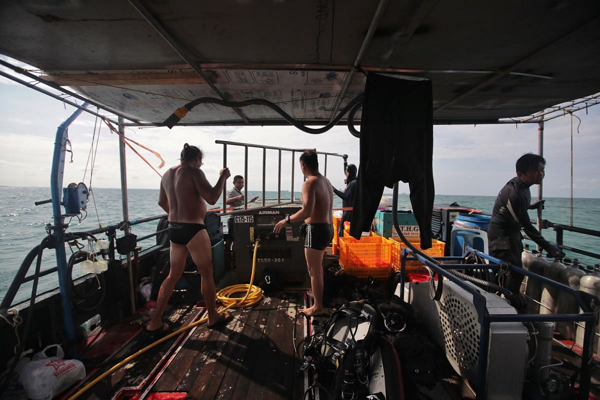 The divers and vessel crew packing up after a long day's work and preparing to head back to the mainland. Divers Andre-Nichol Christian (left), 51, and Jason Khoo (fourth from left), 46, are bringing the dive ladder back on board, as vessel engineer