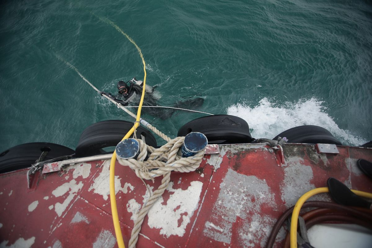 Diver Gideon Liew, 55, holding on to the vessel's mooring line. The line is attached to a heavy object on the seabed and keeps the dive vessel in position. It also acts as a guide for divers finding their way back from the seabed.