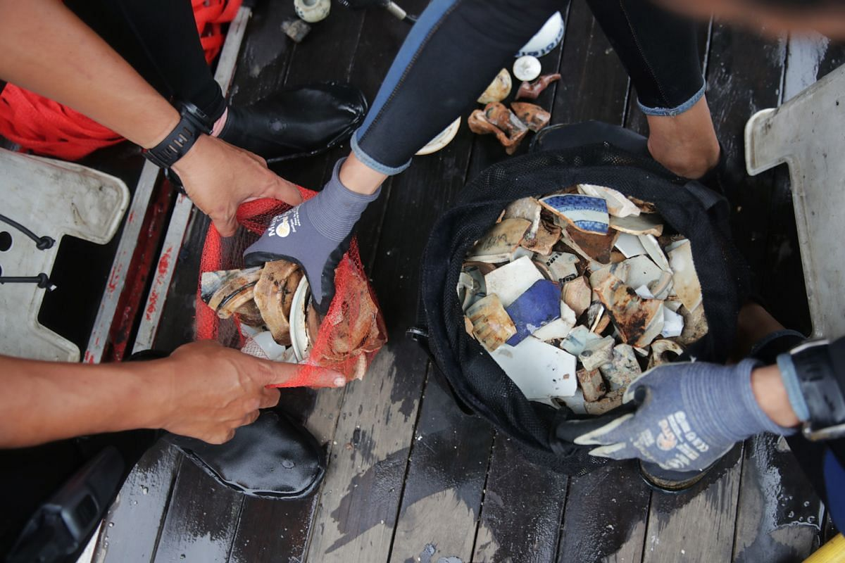 Divers moving ceramic shards from black mesh bags into red mesh bags.