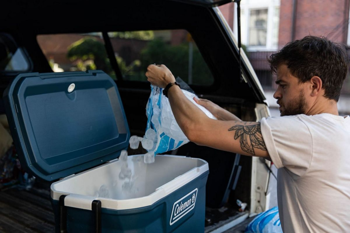 A man fills a cool box with ice during a heatwave in Portland, Oregon, U.S., on June 26, 2021.