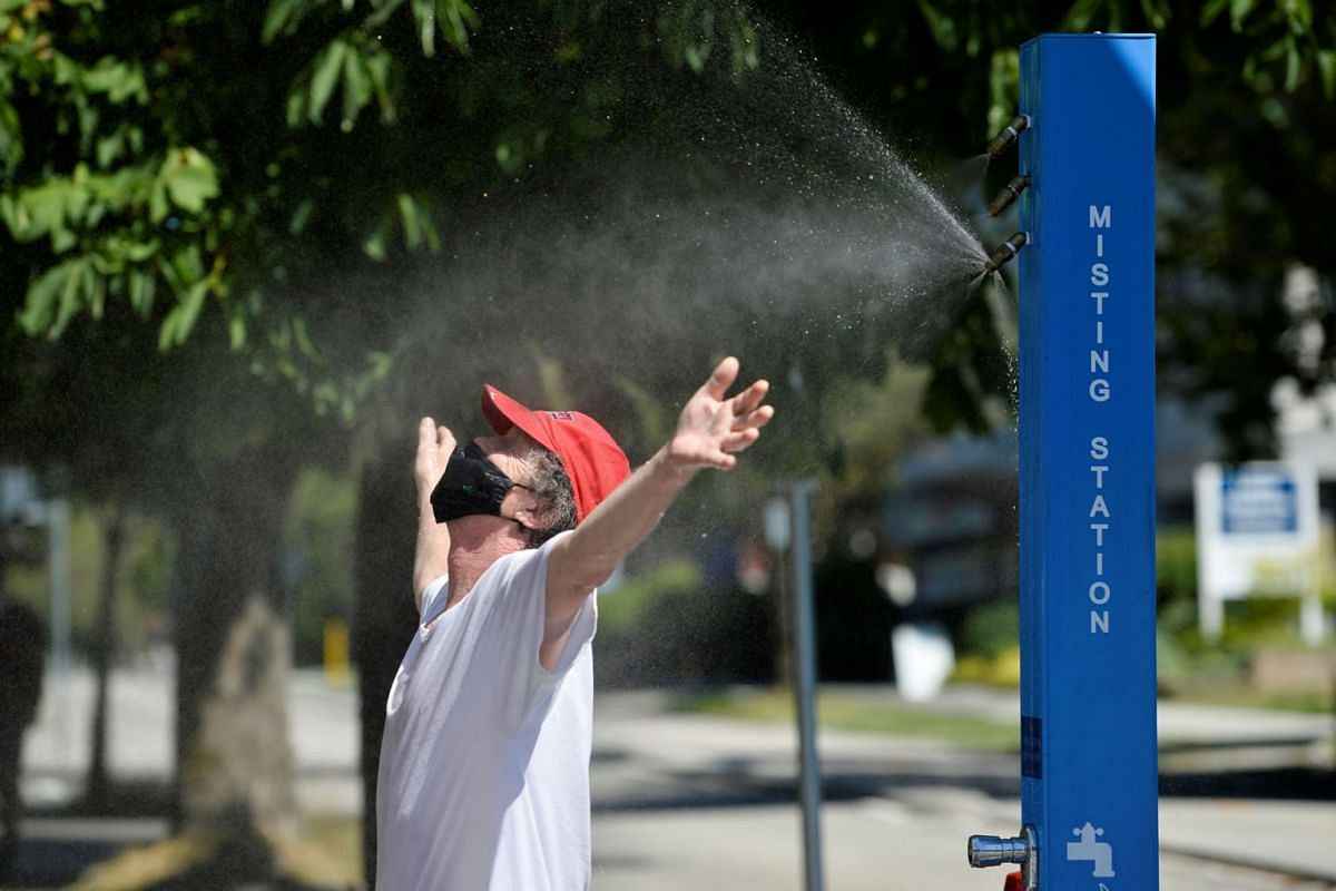 A man cools off at a misting station during a heatwave in Vancouver, British Columbia, Canada, on June 27, 2021.