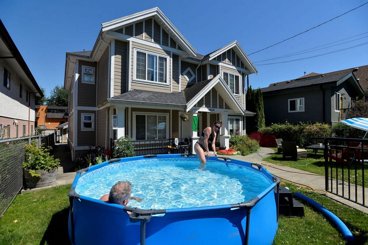 Emily Beers and Craig Patterson cool off in a pool set up in front of Patterson's home during the scorching weather in Vancouver, British Columbia, Canada, June 27, 2021.