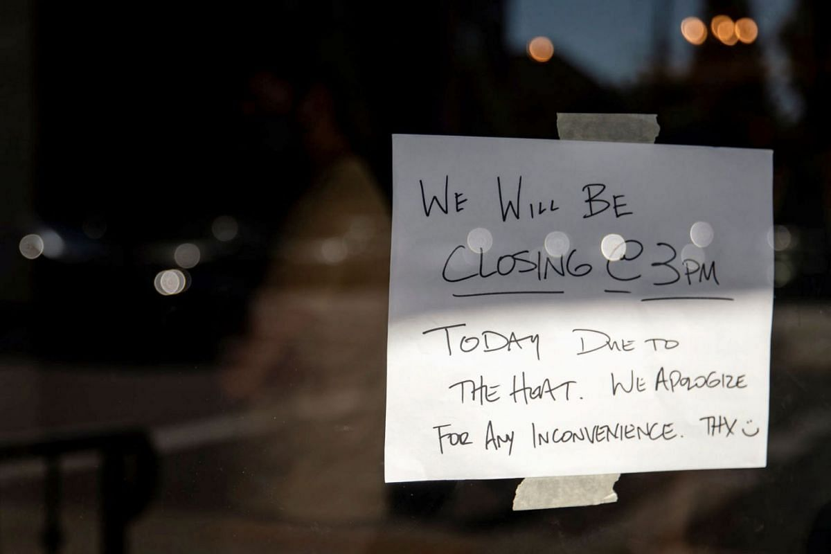 A notice is seen as a business chose to close early due to an unprecedented heat wave in Portland, Oregon, U.S., June 27, 2021.