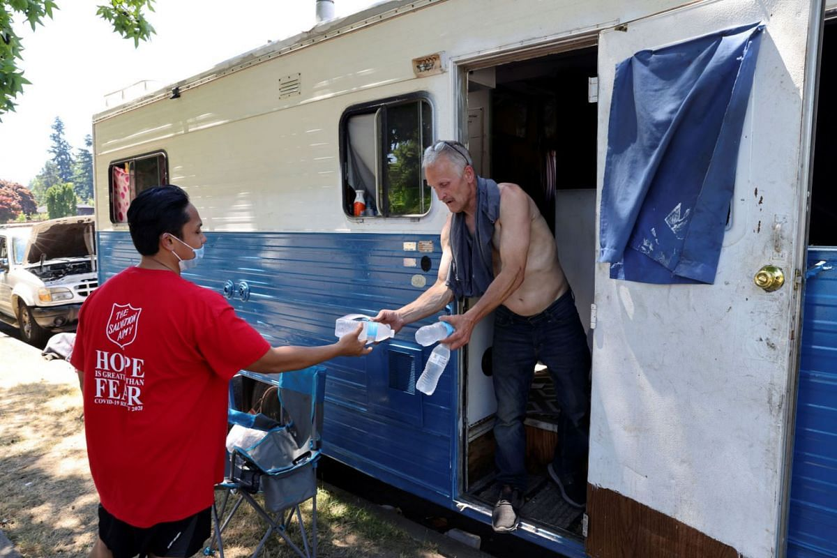 Shanton Alcaraz from the Salvation Army Northwest Division gives bottled water to Eddy Norby who lives in an RV and invites him to their nearby cooling center for food and beverages during a heat wave in Seattle, Washington, U.S., June 27, 2021.