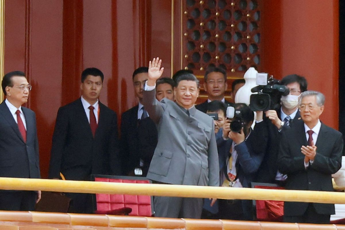 Chinese President Xi Jinping waves next to Premier Li Keqiang and former president Hu Jintao at the end of the event marking the 100th founding anniversary of the Communist Party of China, on Tiananmen Square in Beijing, China July 1, 2021.