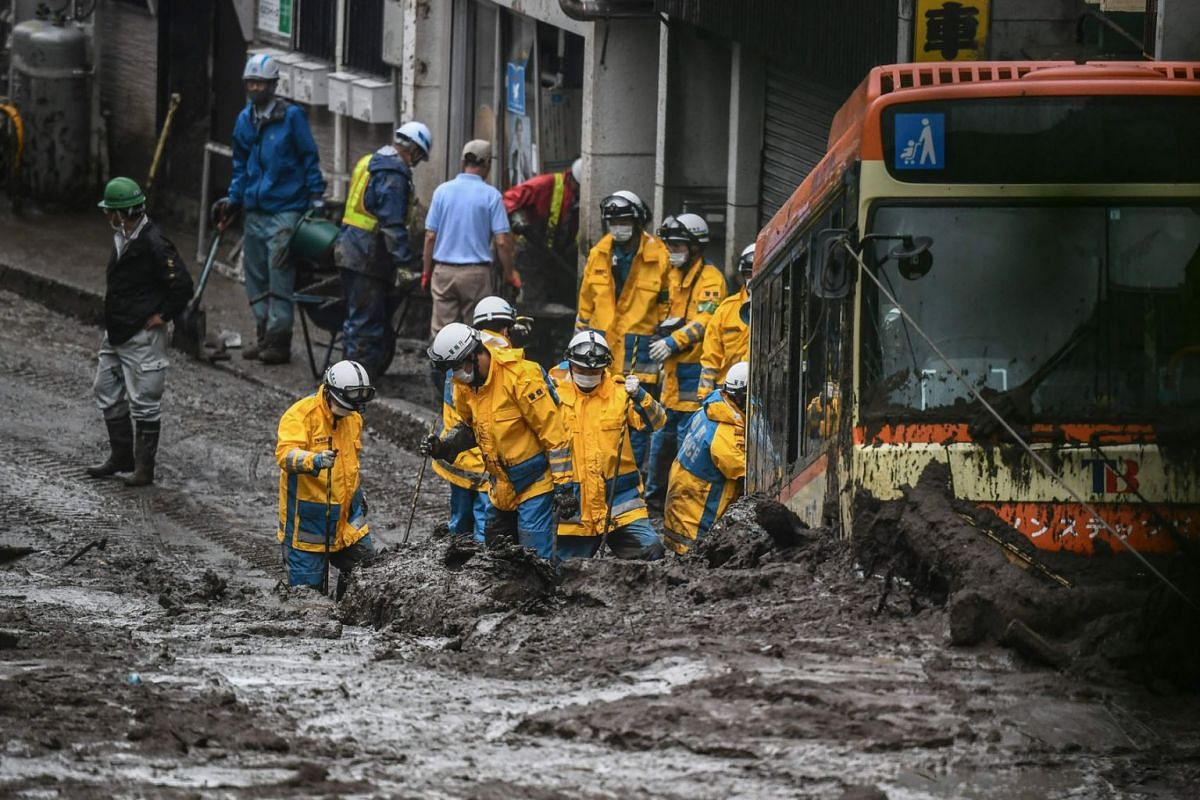 Police search for missing people at the scene of a landslide following days of heavy rain in Atami in Shizuoka Prefecture on July 4, 2021.