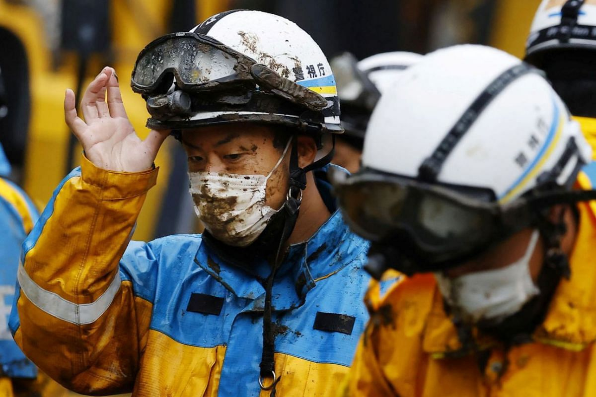 Police officers wearing muddy protective face masks conduct rescue and search operation at the site of a mudslide caused by heavy rain at Izusan district in Atami, Japan July 4, 2021.