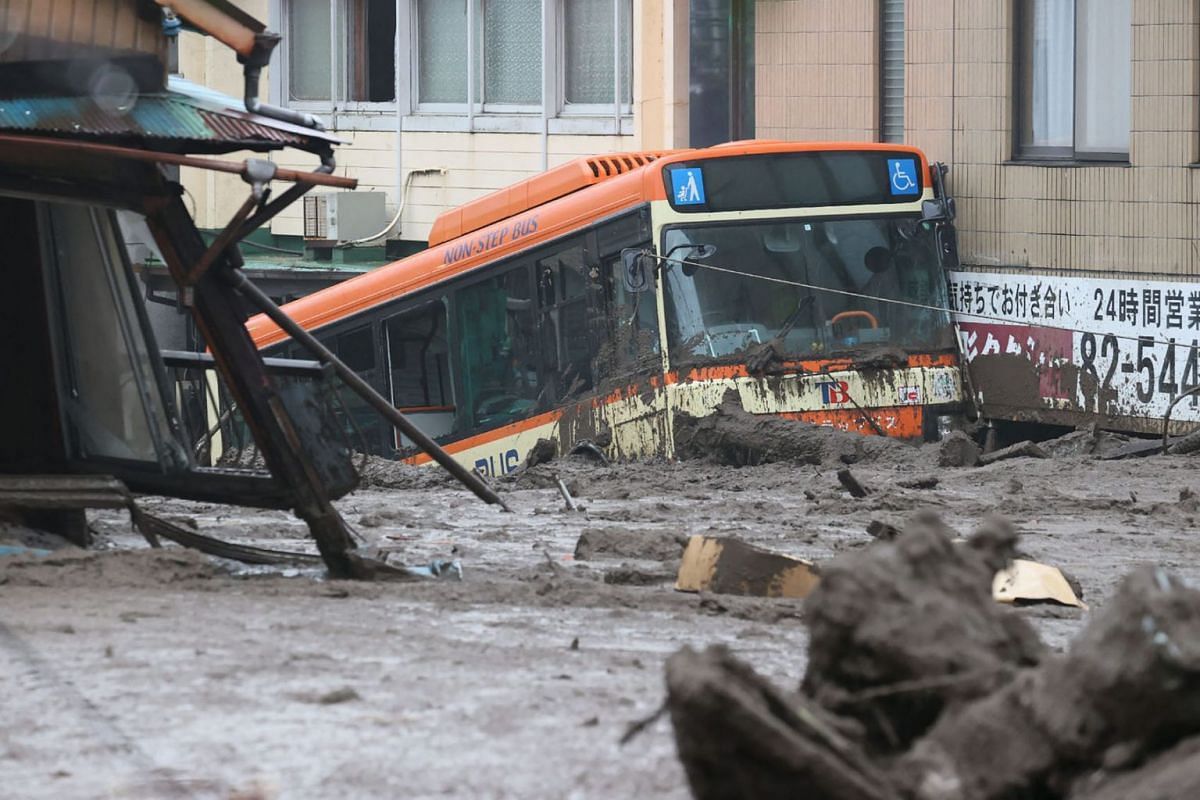 A bus and other debris swept away by a landslide is seen along a road following days of heavy rain in the Izusan area of Atami in Shizuoka Prefecture on July 4, 2021.
