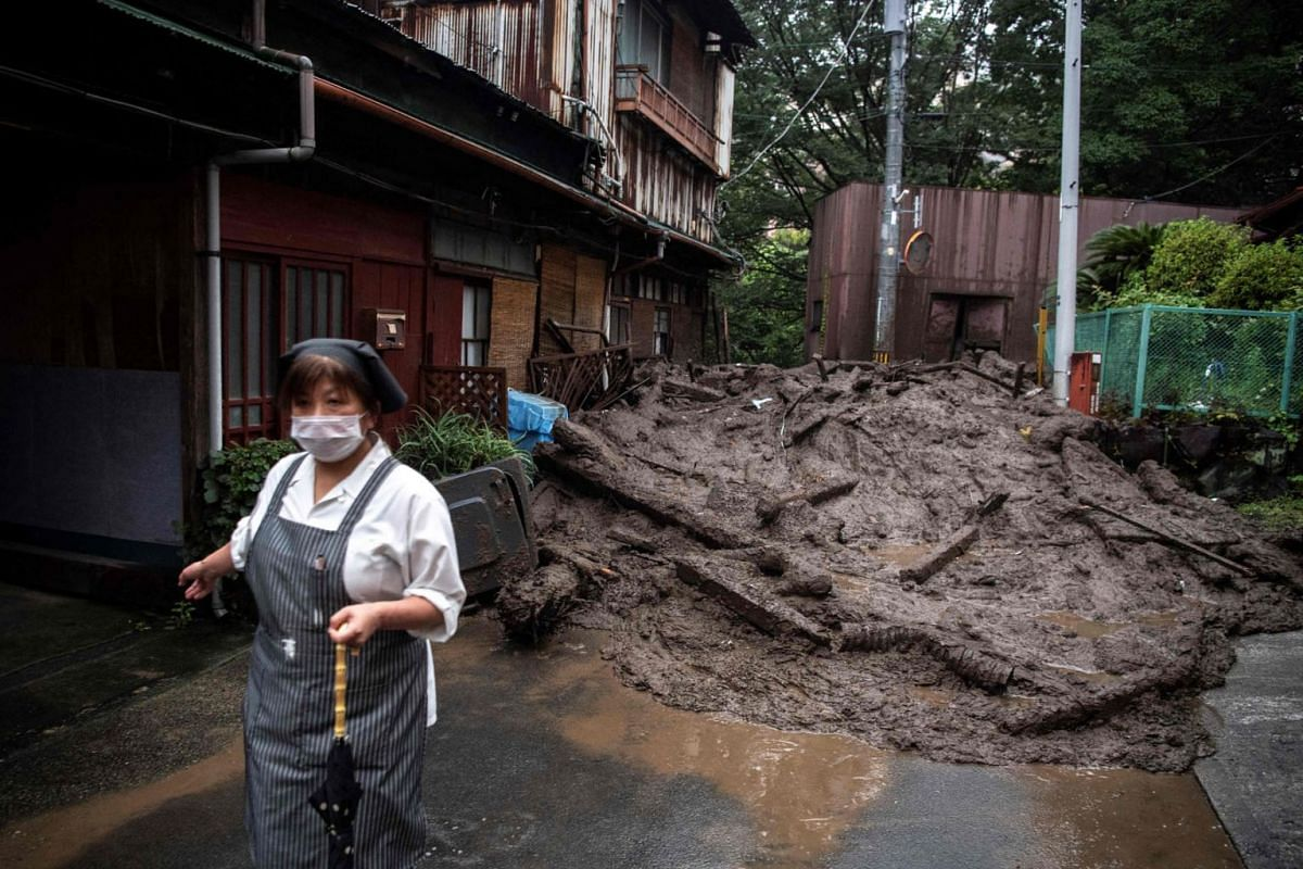 A resident stands near mud and debris at the scene of a landslide following days of heavy rain in Atami in Shizuoka Prefecture on July 3, 2021.