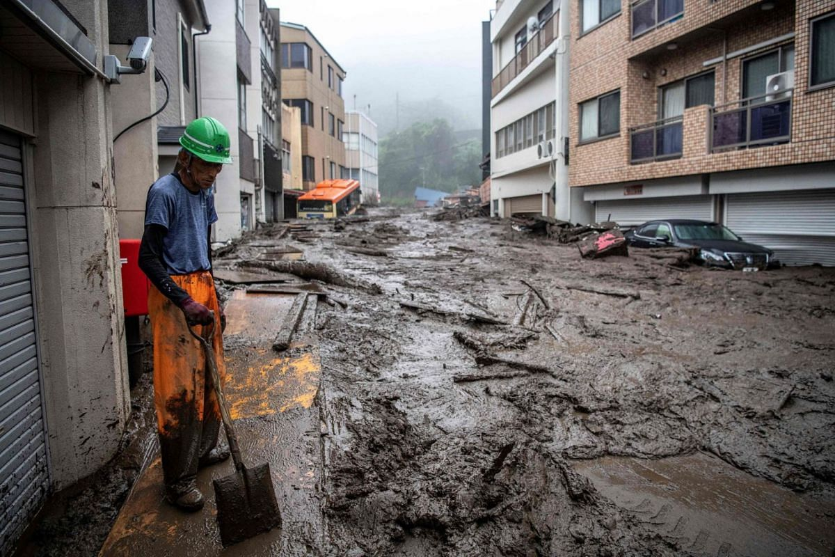 A rescue worker removes mud and debris at the scene of a landslide following days of heavy rain in Atami in Shizuoka Prefecture on July 3, 2021.