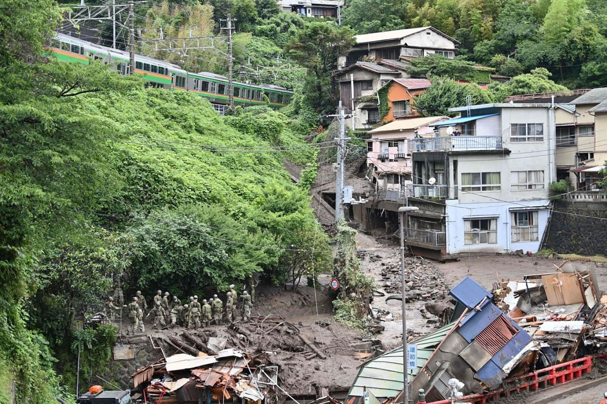 Japan Self-Defense Force personnel search for missing people at the scene of a landslide following days of heavy rain in Atami in Shizuoka Prefecture on July 5, 2021.