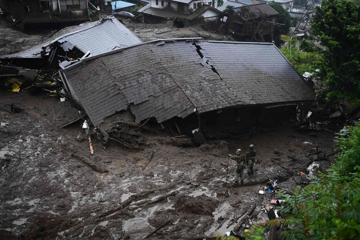 Members of Japan's Self-Defense Forces search for missing people in the mud near a collapsed building at the scene of a landslide following days of heavy rain in Atami in Shizuoka Prefecture on July 4, 2021.