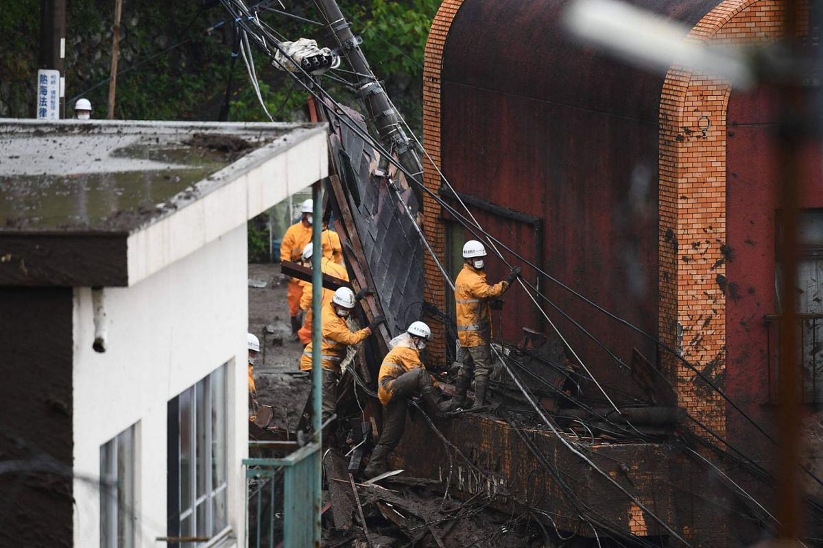 Firefighters search for missing people at the scene of a landslide following days of heavy rain in Atami in Shizuoka Prefecture on July 4, 2021.
