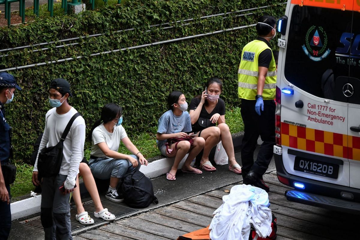 Passengers involved in the accident are seen next to an ambulance at the Bukit Batok bus interchange on July 11, 2021.