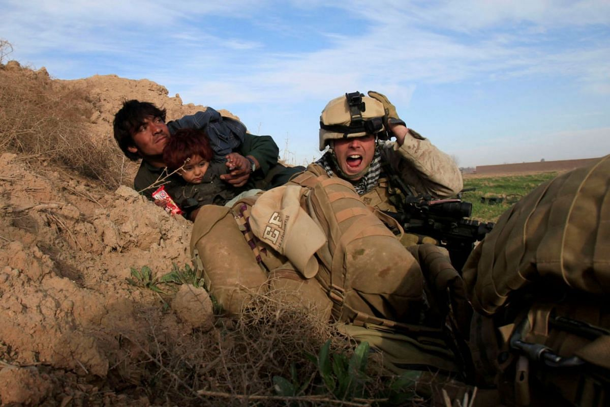 U.S. Marine Lance Corporal Chris Sanderson, from Flemington, New Jersey shouts as he tries to protect an Afghan man and his child after Taliban fighters opened fire in the town of Marjah, in Nad Ali district, Helmand province, Afghanistan, February 1