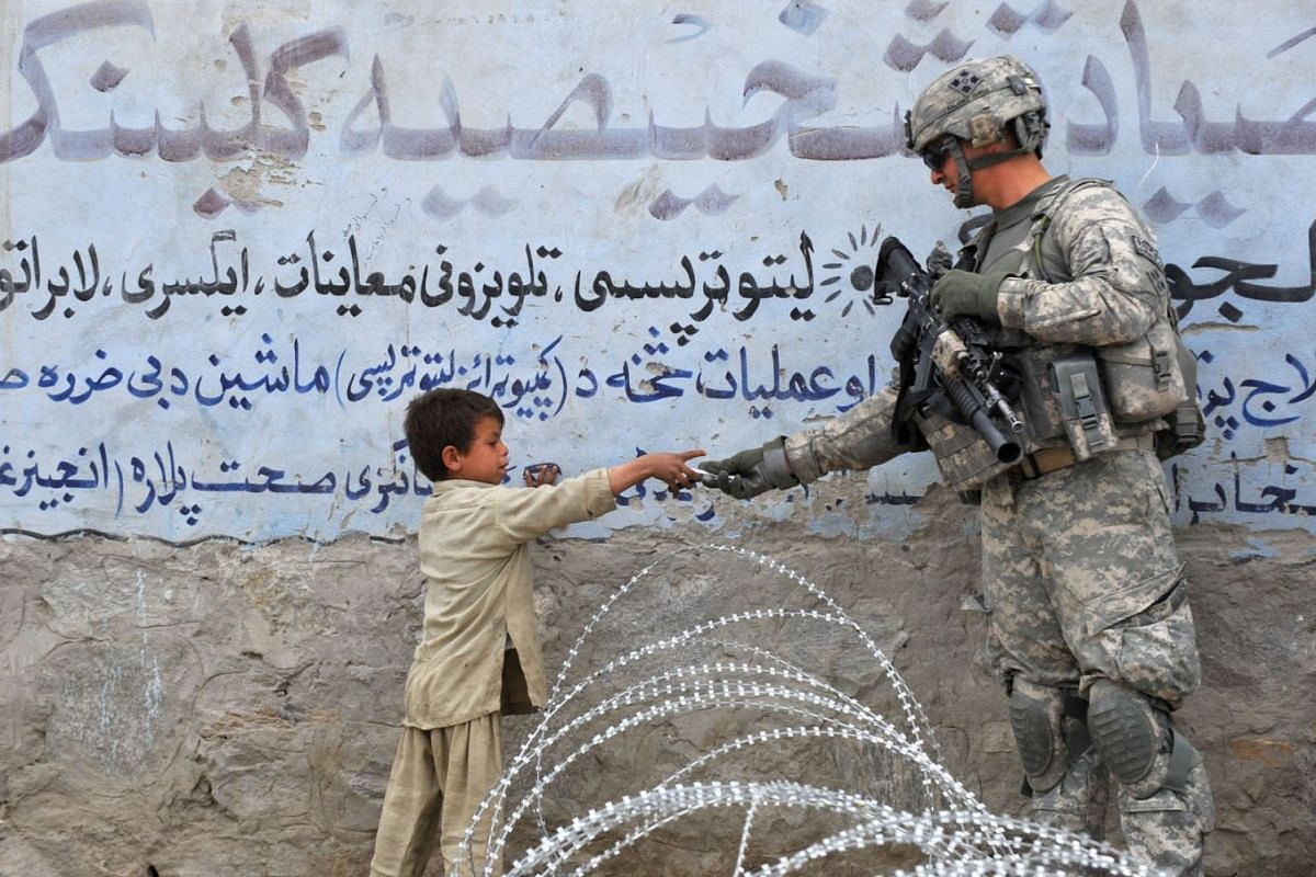 A US soldier from 4th Infantry Division 4 Brigade Alpha Company presents a gift to an Afghan child during a patrol at Khogyani in Nangarhar, February 20, 2010.