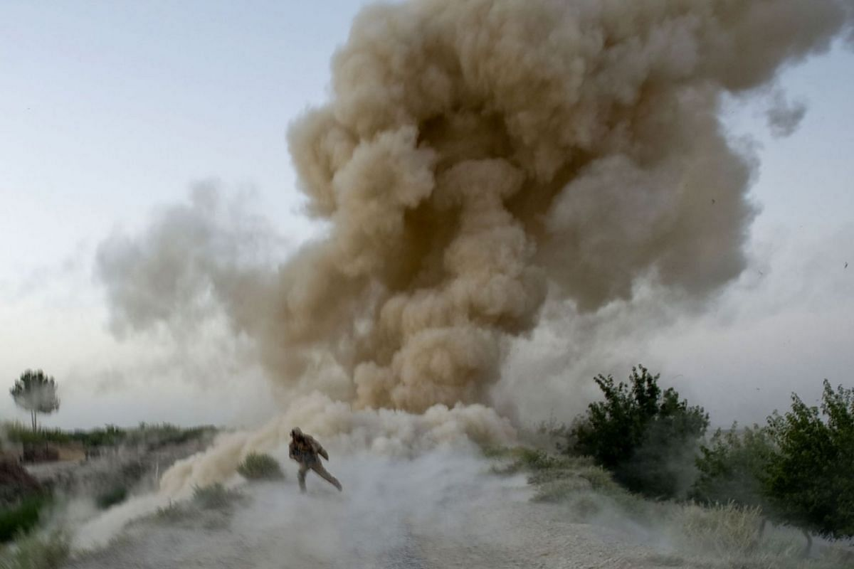 US Marine Sergeant Anthony Zabala of 1st Combat Engineering Battalion of 2nd Marine Expeditionary Brigade runs to safety as an Improvised Explosive Device (IED) explodes in Garmsir district of Helmand Province, July 13, 2009.