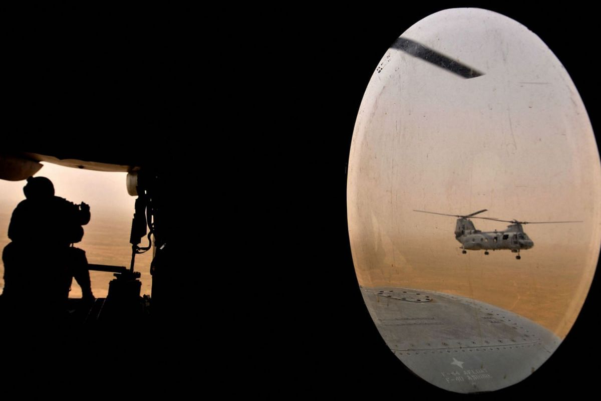 A US soldier (L) sits in the rear of a Marine Chinook helicopter while flying over Camp Bastion in Helmand province, southwest of Kabul, May 3, 2008.