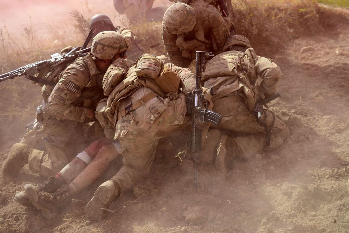 US soldiers operating under the North Atlantic Treaty Organisation sponsored International Security Assistance Force protecting a wounded comrade from dust and smoke flares after an improvised explosive device blast during a patrol near Baraki Barak