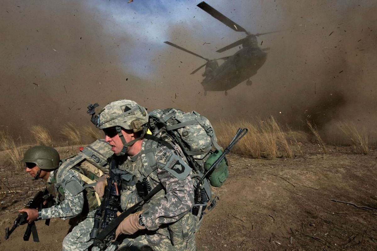 A US Army soldier and an Afghan National Army soldier race to get out of the way of a CH-47 Chinook helicopter landing in hostile territory in the Spira mountains in Khost province, November 11, 2009.
