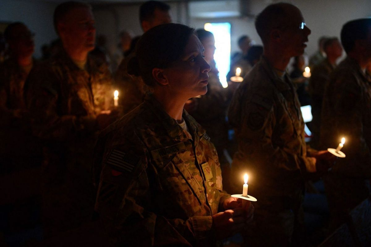 US soldiers hold candles as they attend a religious ceremony on Christmas Eve at a US military base in Kabul, December 24, 2013.