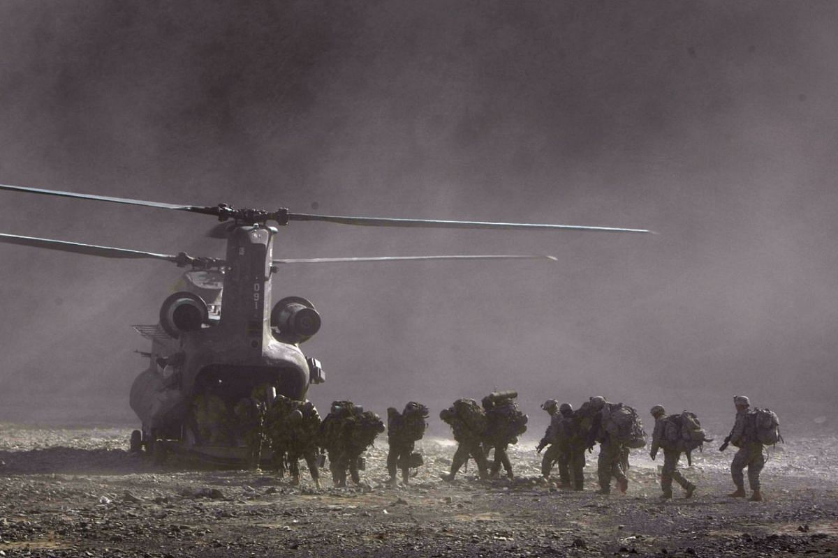 US Army soldiers from 2-506 Infantry 101st Airborne Division and Afghan National Policemen and Army load onto a UH-47 Chinook helicopter landing to pick them up during day three of Operation Shir Pacha into the Derezda Valley in the rugged Spira moun