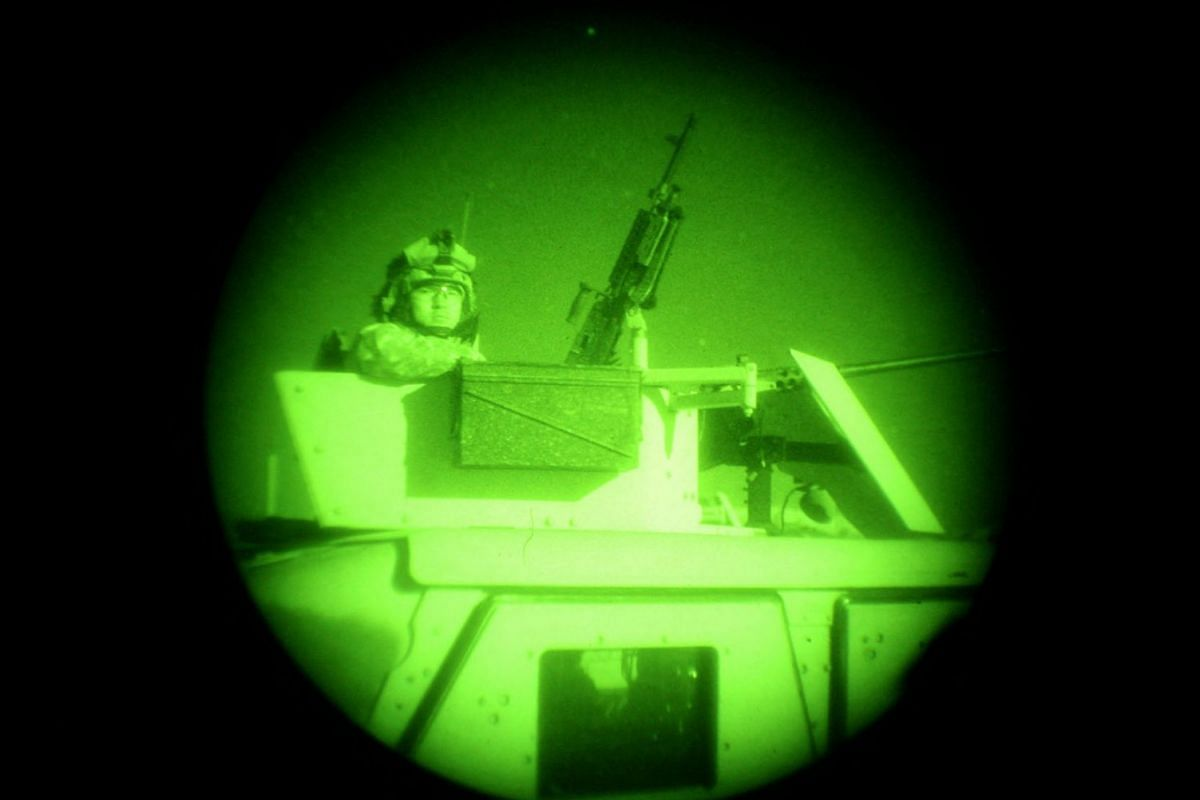 US soldiers from 1st Battalion, 32 Infantry Regiment (1-32), attached to 4th Battalion, 25 Field Artillery, (4-25), 10th Mountain Division, are seen through a night vision scope following a search of a compound near Khowst in Paktia province, Decembe